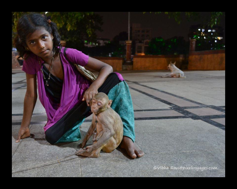 A girl sits with her performing monkey in Mumbai