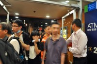 Admiralty Centre. Just after a wave of tear-gas reaches the crowd, the rush into the doors of MacDonald's for shelter. MacDonald's staff members standby to hold the doors open. Customers are in shock