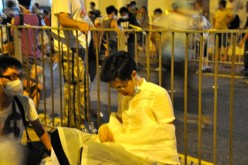 Moments after a wave of tear-gas reaches Admiralty, a young man falls sick on the side of the road. His friend keeps watch at his side
