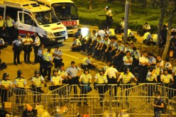 Police congregate and rest on a road side. Officers with helmets on duty keep stoic faces.