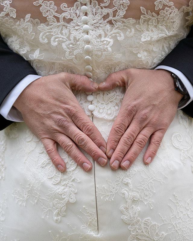 brudgum-gör-hjärta-med händer-på brudens-rygg