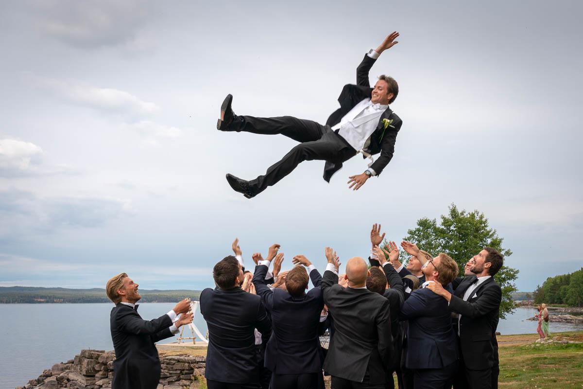 Brudgummens vänner kastar brudgummen högt upp i luften på bröllopsfest Hillringsbergs Herrgård Arvika