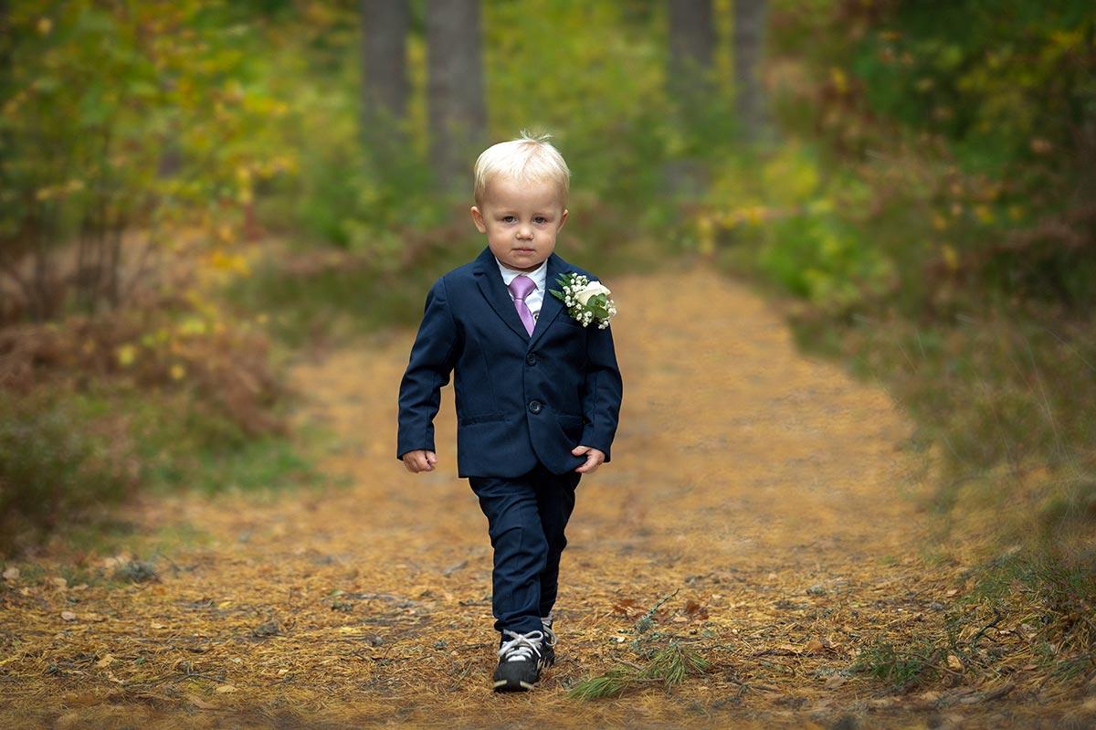 Liten pojke går på stig i skogen iklädd bröllopskläder