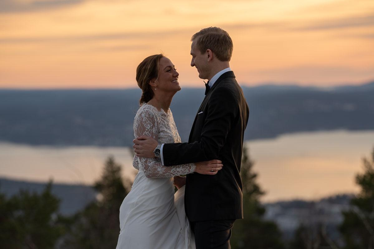Bröllopspar håller om varandra i solnedgången