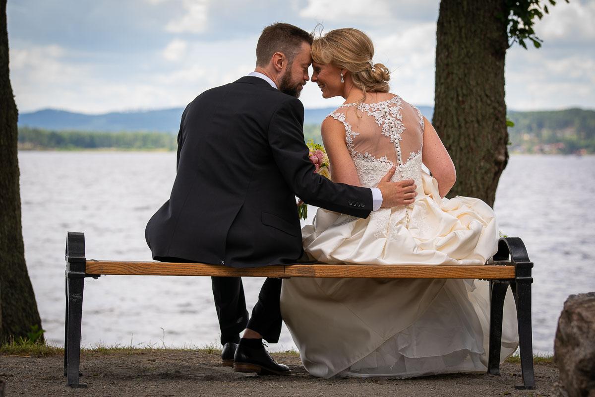 Bröllopspar håller om varandra sittandes på bänk på Sågudden i Arvika