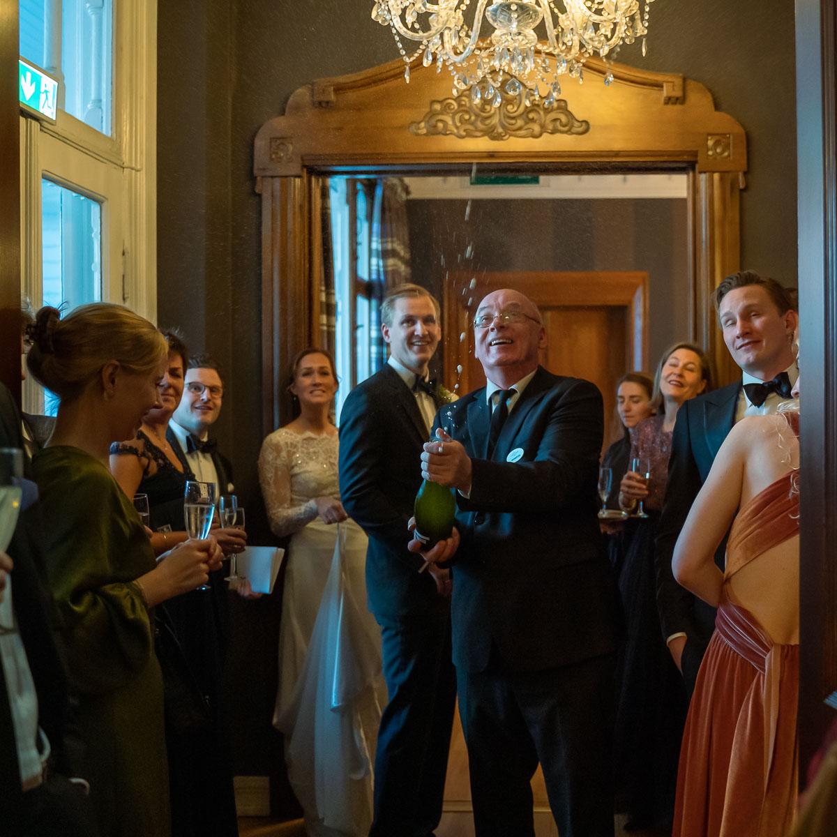 Kyparen öppnar champagneflaskan och korken flyger med gäster och bröllopspar bredvid på bröllopsfest