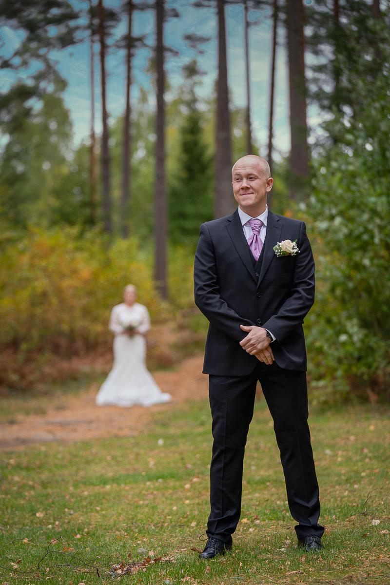 Brudgummen väntar på bruden med bruden bakom honom
