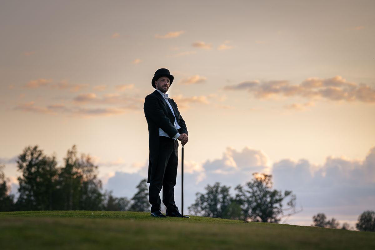 Brudgummen iklädd hatt och med käpp står på gräskulle vid solnedgången