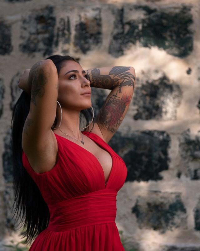kvinna i röd klänning vid stenvägg