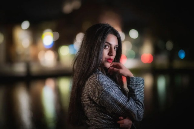 kvinna med kappa och stadsljus i bakgrunden