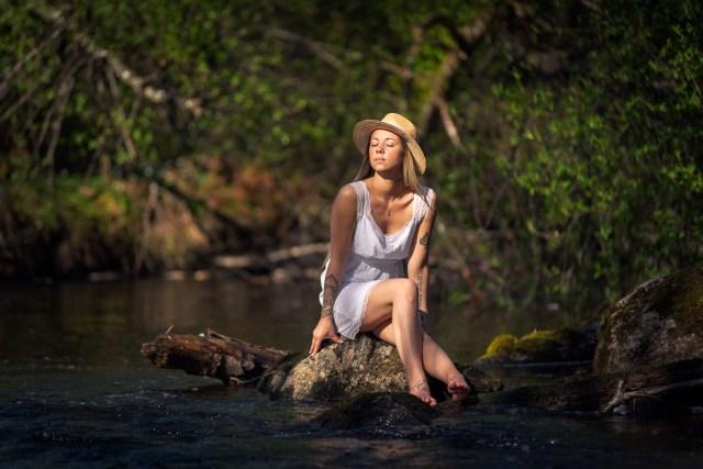 kvinna i vit kjol och hatt sitter vid bäcken och njuter av solen