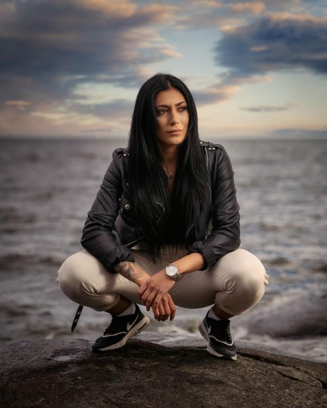 kvinna i svart skinnjacka och vita byxor sitter på huk vid sjön