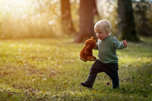 liten pojke springer på gräset med nalle i hand på Sågudden i Arvika