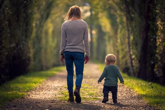 mor och son går bredvid varandra på stig på Viksholmen i Arvika