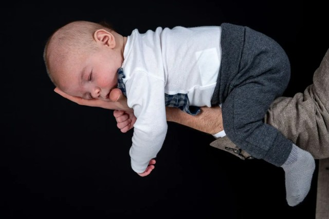 far håller sin sovande lilla pojke i handen