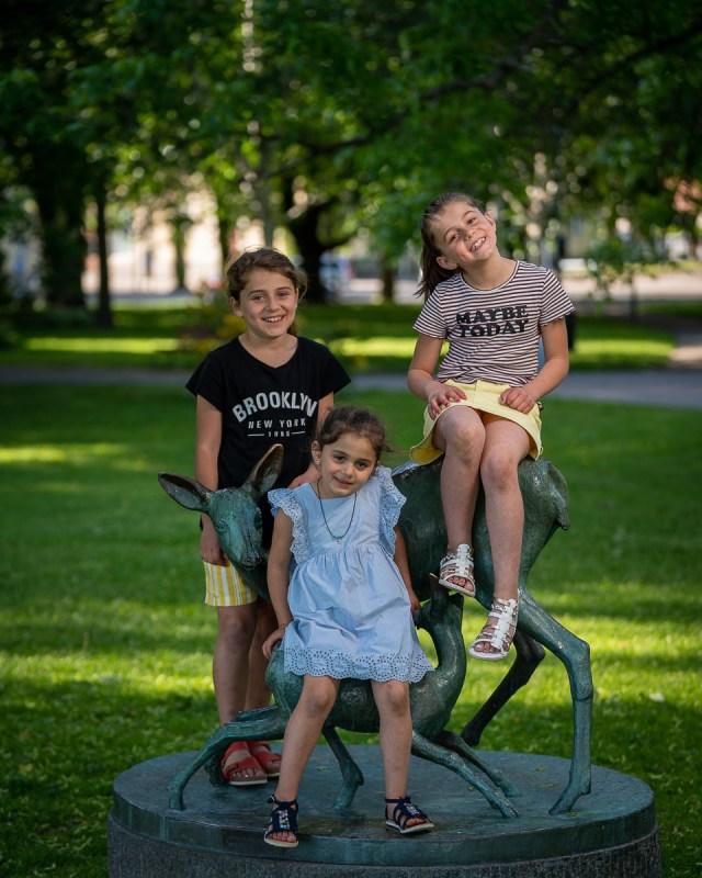tre små flickor på skulptur av rådjur i stadsparken i Arvika