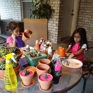 The girls, painting pots while I re-pot my babies.