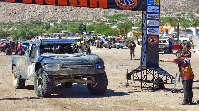 John leaves the starting line at the direction of NORRA Director Mike Pearlman. It was Pearlman's late father Ed, along with others, who established the first running of the NORRA Mexican 1000 off-road rally in November 1967.