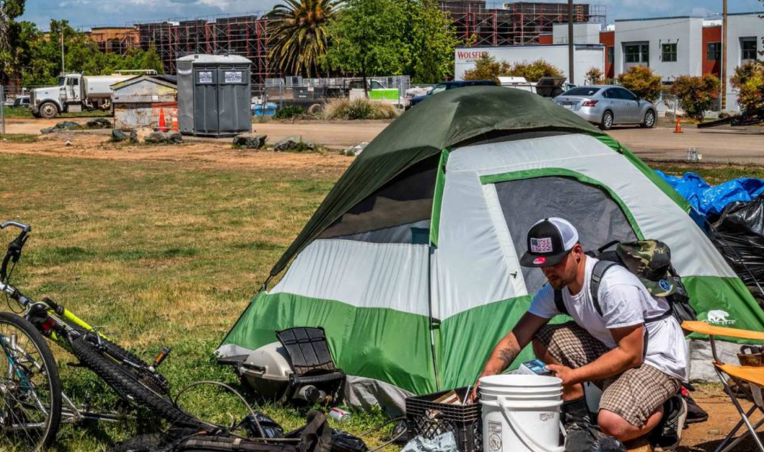 Man outside a tent in a public are near new housing construction