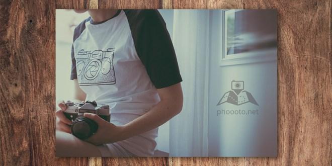 Person mit T-Shirt mit Kamera Motiv und Zenit E in der Hand