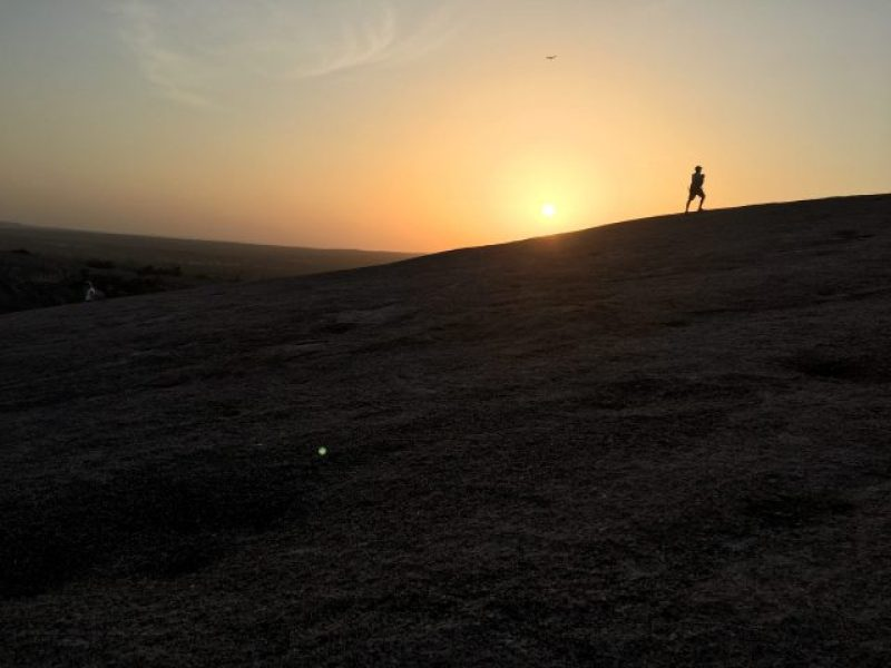 A passerby carrying a young child up Enchanted Rock