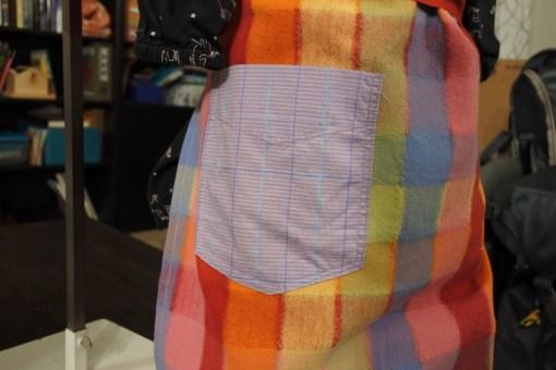 Close up image of a purple plaid pocket on a rainbow plaid apron