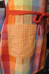 Close up image of an orange pocket on a rainbow plaid apron
