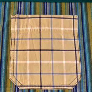 Close up image of a green plaid pocket on a blue striped background