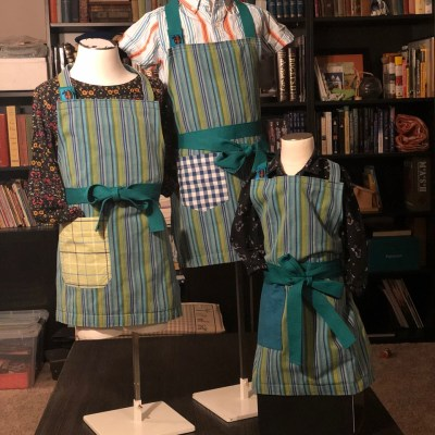 Three mannequins with blue striped aprons.