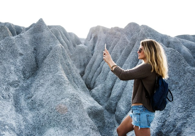 Woman photographing mountains.