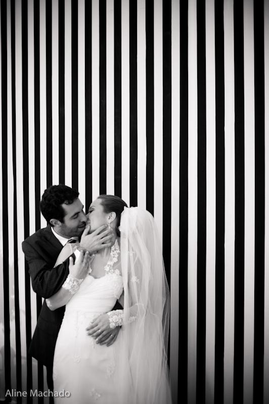 Noivos posam em fundo de listras em casamento. Foto: Aline Machado.