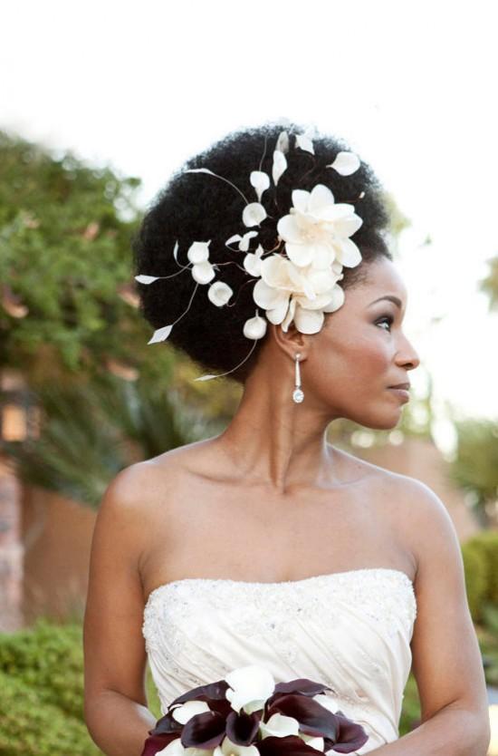 Penteado para noiva negra: balck power afro com acessório de flores brancas na cabeça. Foto: Boutique De Bandeaux.