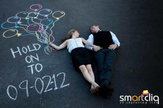 Save-the-date fotográrico, com casal deitado no chão e desenho em giz com balões. Foto: Smartcliq.