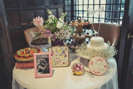 Mesa de doces para casamento alternativo: bolo rústico, bordados e porta-retratos. Foto: Lisa Jane.