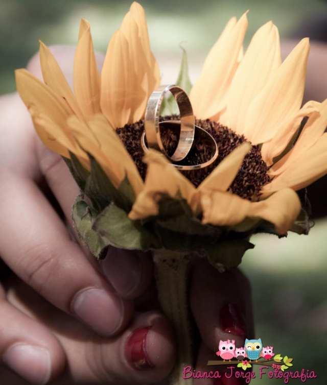 E-session (fotos de noivado): alianças de casamento no girassol. Foto: Bianca Jorge Fotografia.