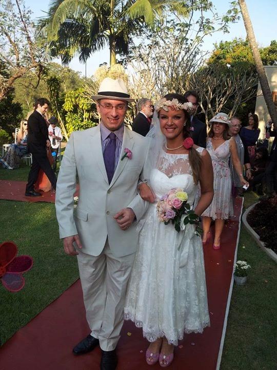 Casamento no campo: noiva com coroa de flores e vestido longuete vintage, noivo com chapéu e terno creme.