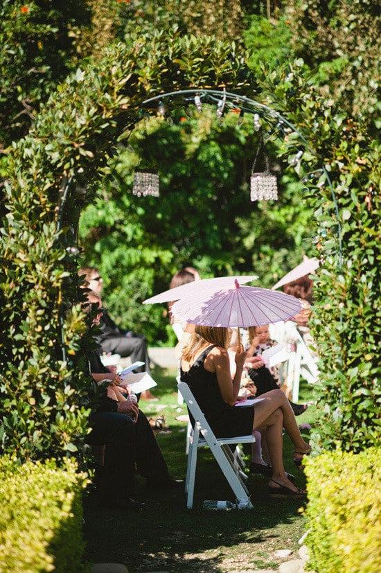 Convidada com sombrinha oriental em casamento no campo. Foto: Paul Von Rieter.
