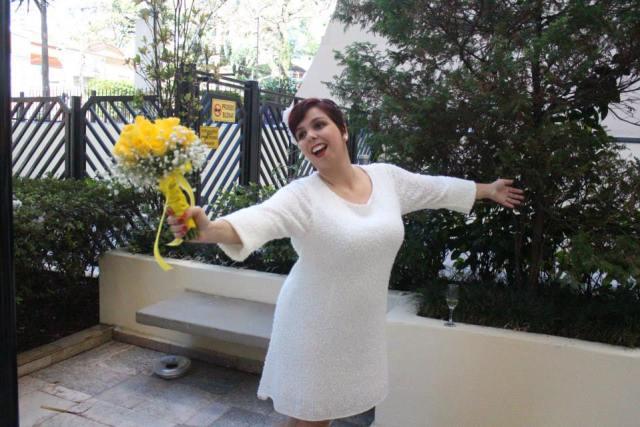 Vestido de noiva curto com manga comprida.