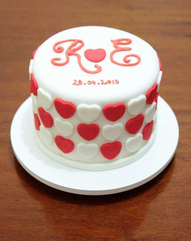 Bolo de noivado ou chá bar: decorado em pasta americana, com corações vermelhos e brancos e as iniciais dos nomes dos noivos com a data do casamento. Foto e bolo: Nena Chocolates.