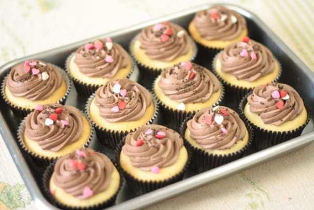 Cupcakes de massa branca, cobertura de chocolate e confeitos de coração. Foto e doces: Nena Chocolates.