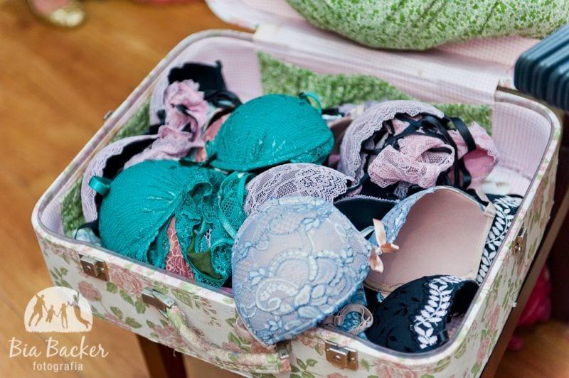 Decoração de chá de lingerie com sutiãs em mala vintage. Foto: Bia Becker.