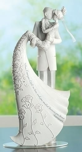 Noivinhos de topo de bolo em porcelana dando beijo.