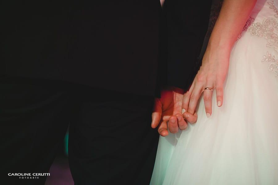 Noivos de mãos dadas no altar. Foto: Caroline Cerutti.