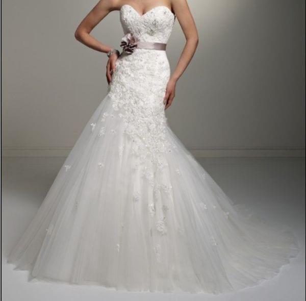 Vestido de noiva tomara que caia com saia de tule e faixa na cintura.