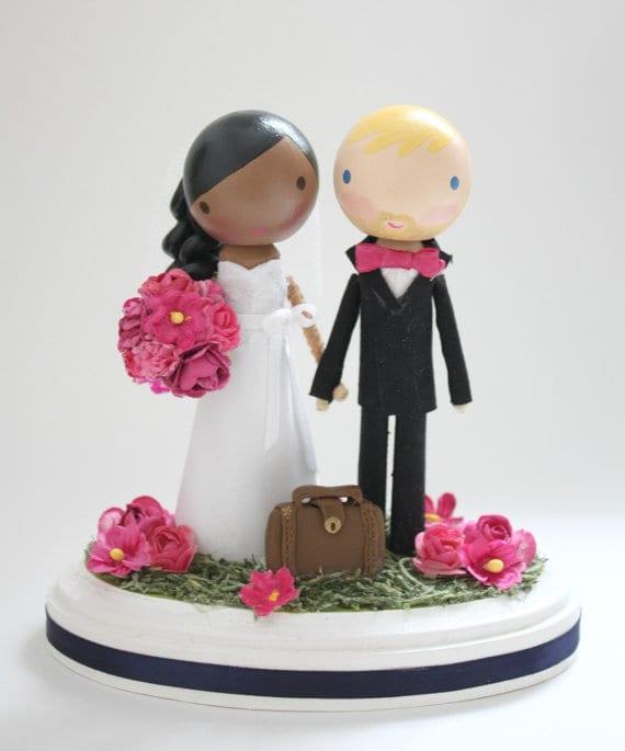 Noivinhos de topo de bolo em madeira da Lollipop Workshop. Noiva negra, com buquê rosa, noivo loiro, de gravata borboleta rosa.