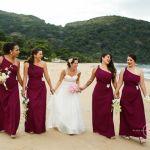 Casamento na praia Tabi e Carlos: noiva e madrinhas de casamento com vestido igual combinando vinho. Foto: André Pinnola