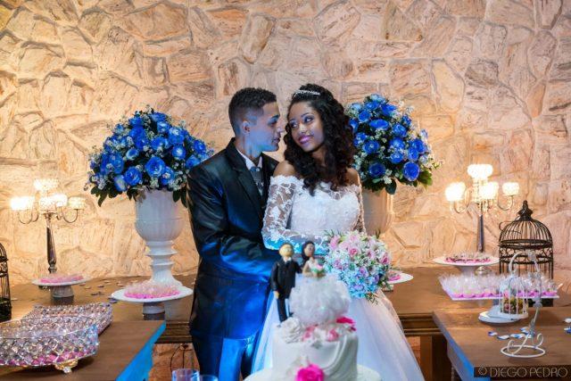 Decoração de casamento azul e rosa na mesa do bolo. Vestido de noiva com manga comprida. Casamento Naara e Rodrigo. Foto: Diego Pedro.