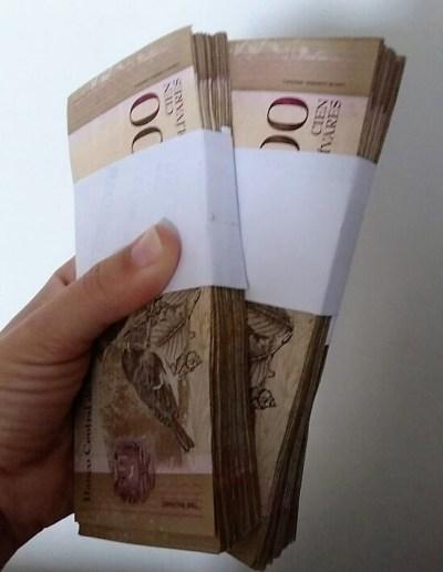 Mão segura notas de moeda venezuelana