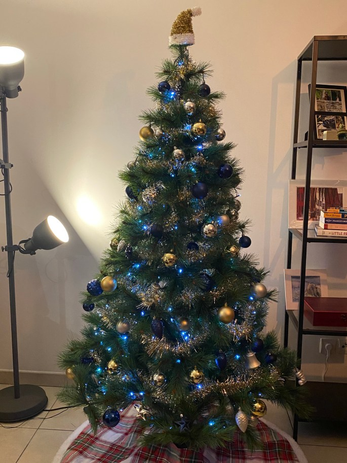 A GOLD, SILVER, AND BLUE CHRISTMAS TREE DECORATED COVID CHRISTMAS SEASON
