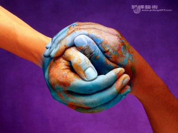 Duas pessoas unem as mãos na forma de um globo em gesto de paz